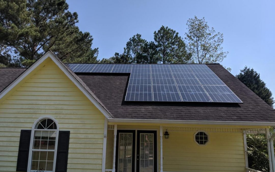 Yellow house with multiple solar panels on the roof